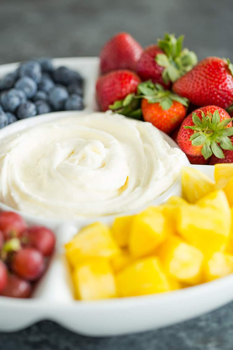 A fruit platter with fruit dip in the center.
