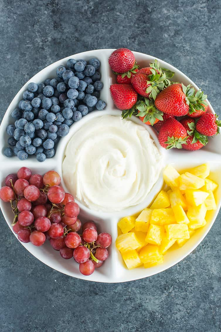 A platter of blueberries, strawberries, grapes and pineapple with fruit dip in the middle.