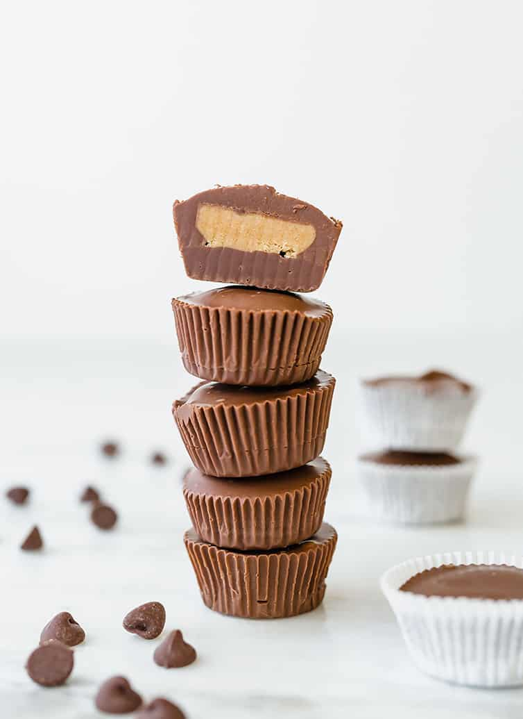 A stack of five peanut butter cups, with the top one sliced in half with filling exposed.