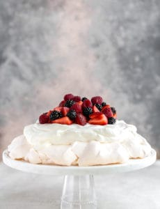 Pavlova on a glass cake plate, with whipped cream and berries.