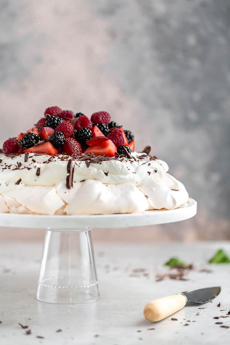 Pavlova on a serving plate with whipped cream, berries, and shaved chocolate.