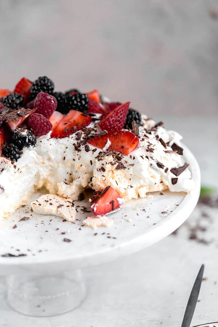 Pavlova on a serving plate that has been sliced and served.