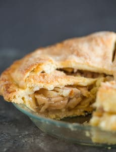 A fresh baked apple pie sliced into so you can see the filling.