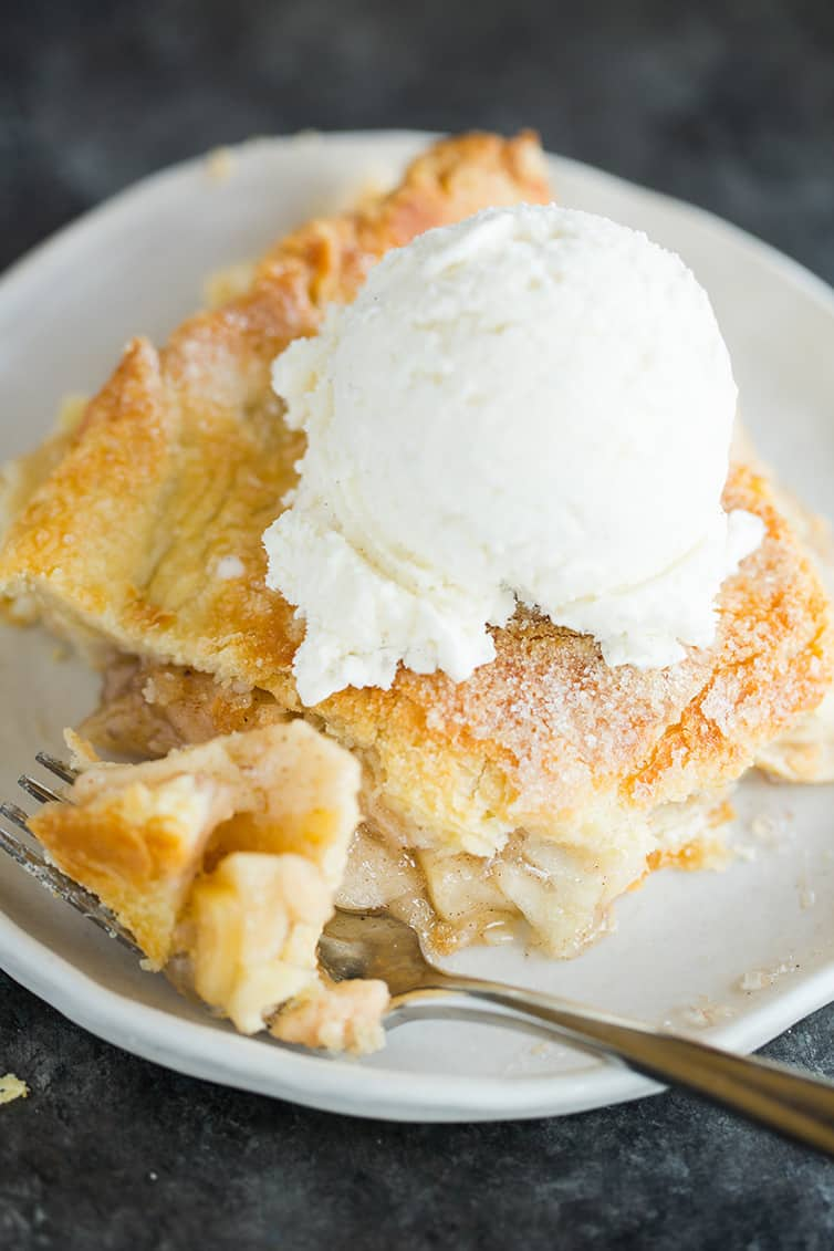 A slice of apple pie with a scoop of vanilla ice cream on top.