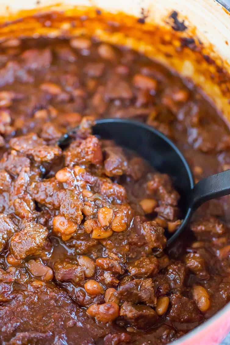 Chili con carne in a pot, with a ladle scooping some out.