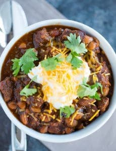 A bowl of chili con carne topped with sour cream, shredded cheese and cilantro.