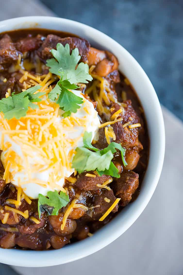 A close up shot of a bowl of chili con carne with sour cream, shredded cheese and cilantro on top.