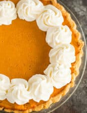 An overhead shot of a sweet potato pie with whipped cream around the borders.