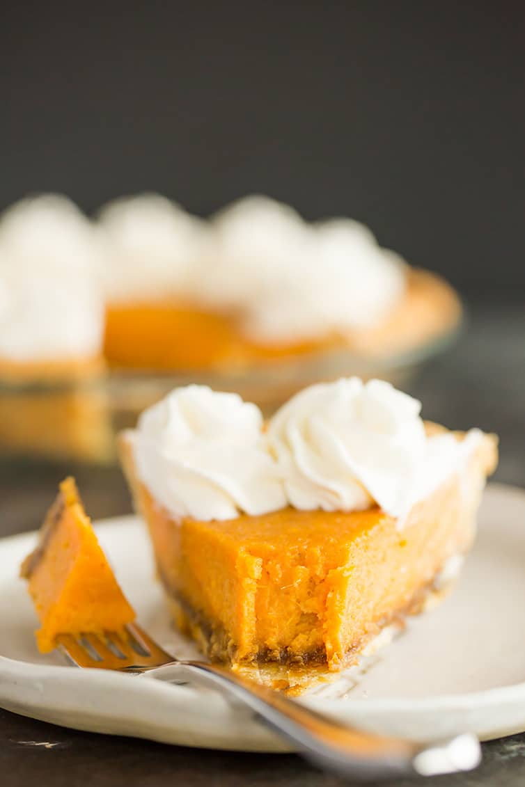 A slice of sweet potato pie with a forkful taken out.
