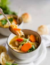 A spoonful of chicken noodle soup with carrot and egg noodle.