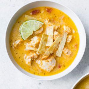 An overhead shot of a bowl of chicken tortilla soup.