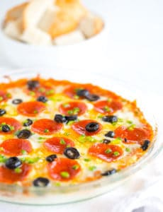 A pie plate with pizza dip and a bowl of bread cubes for dipping.