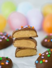 Peanut butter eggs, cut in half and stacked with Easter eggs in the background.