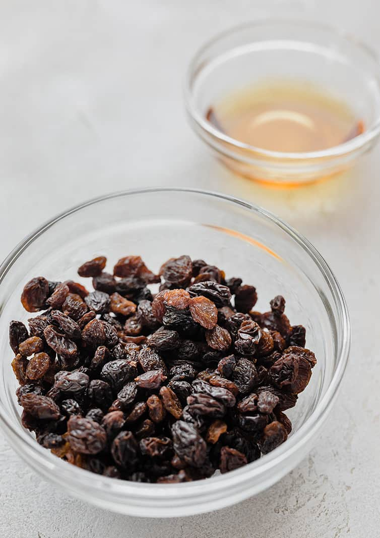 A bowl of raisins with a smaller bowl of bourbon.