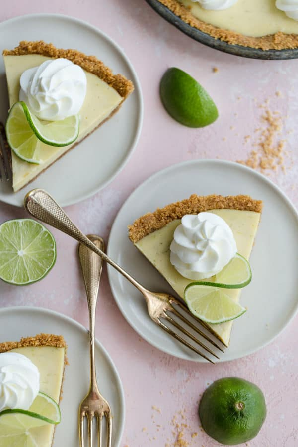 Individual slices of key lime pie on dessert plates with forks.