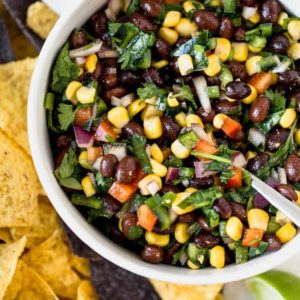 A bowl of black bean salsa with tortilla chips surrounding it.
