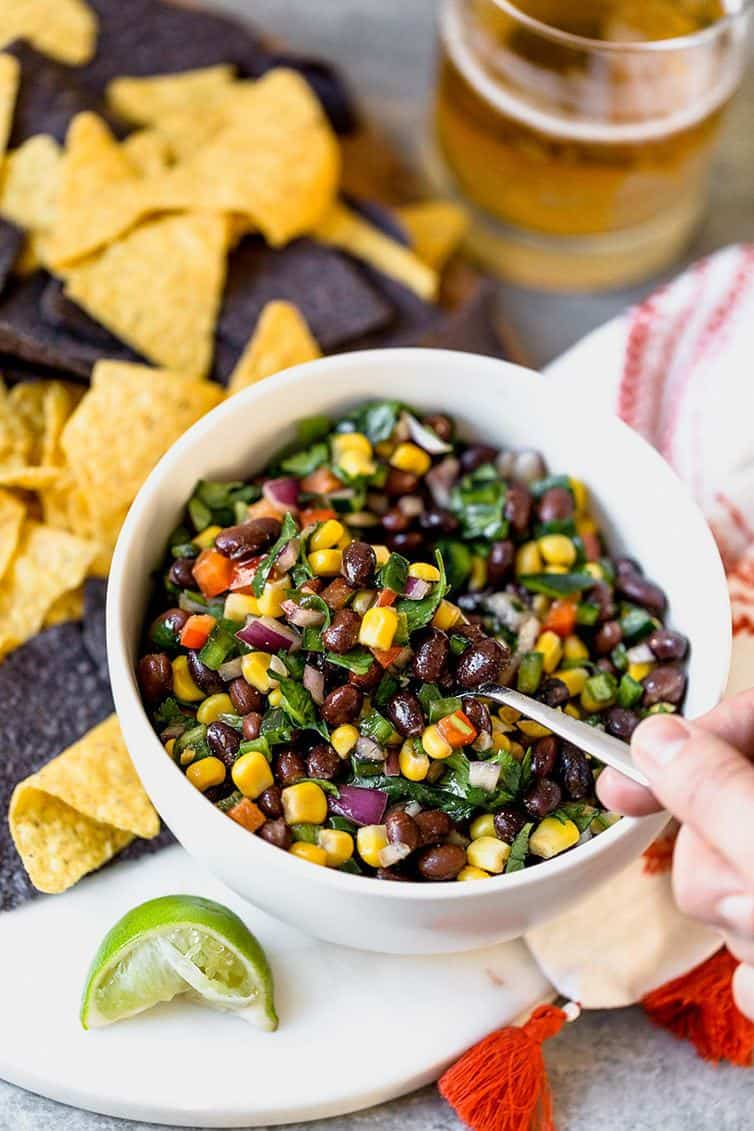 A bowl of black bean salsa with a hand scooping a spoonful.