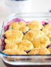Baked blueberry cobbler in a glass pan with a bowl of blueberries in the background.