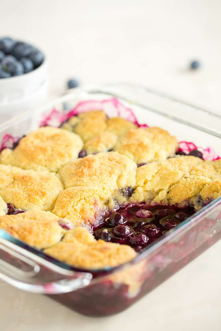 A pan of blueberry cobbler with a big scoop taken out.