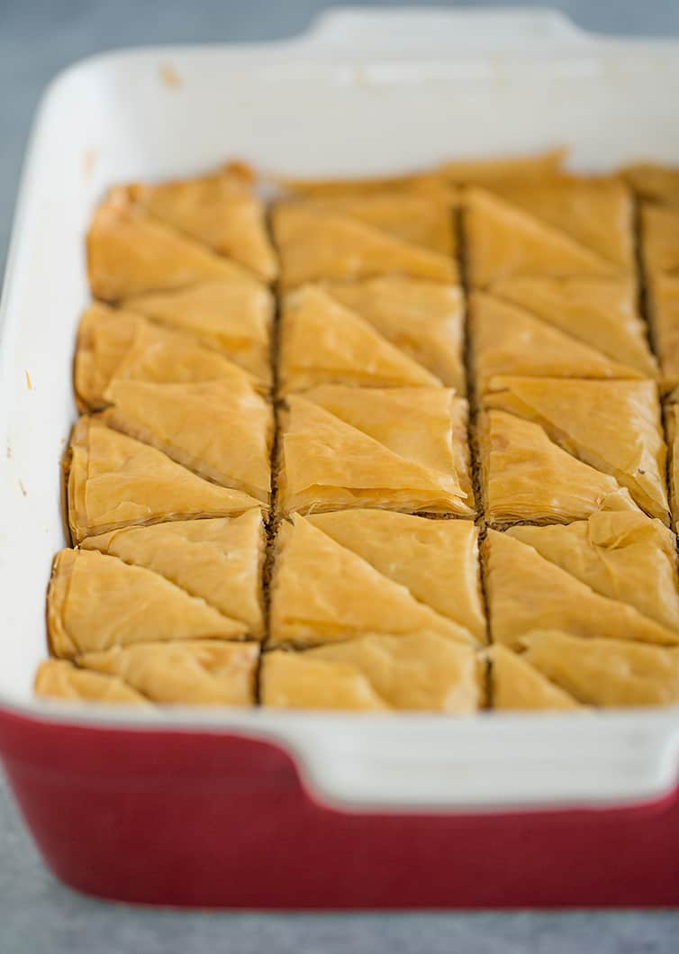 A tray of baklava out of the oven, cut into triangles.