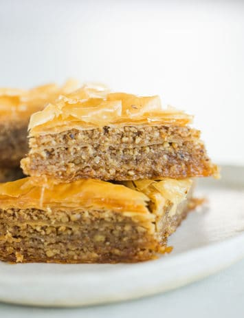 Triangles of baklava stacked on a plate.