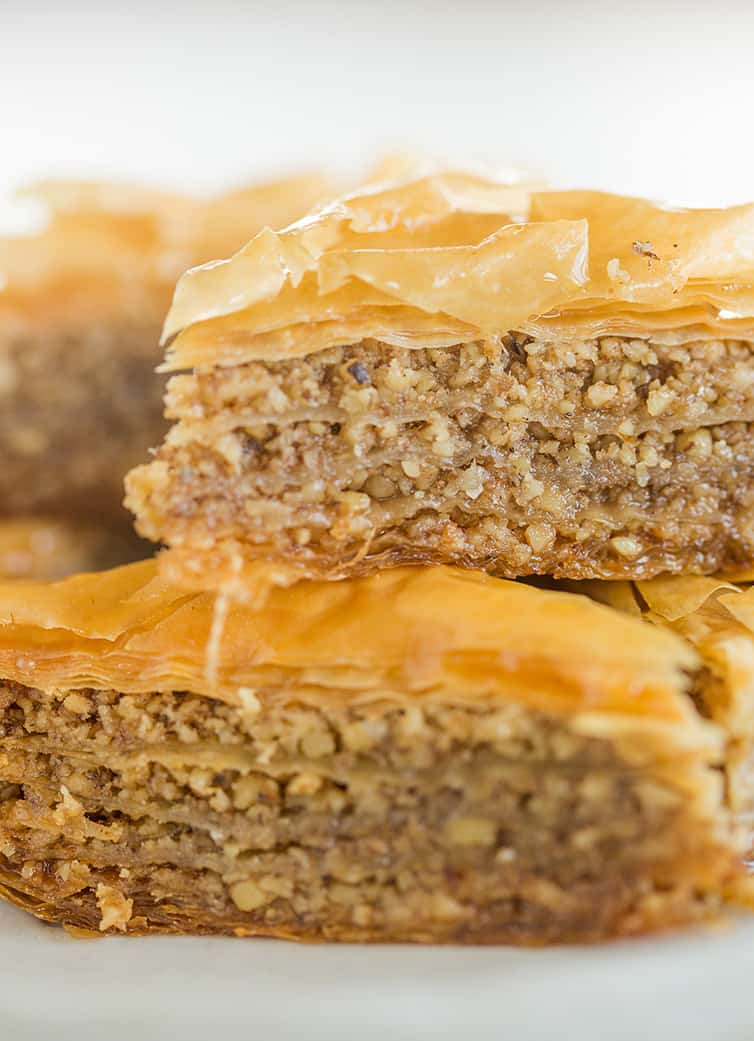 A close up photo of two pieces of baklava stacked on top of one another.