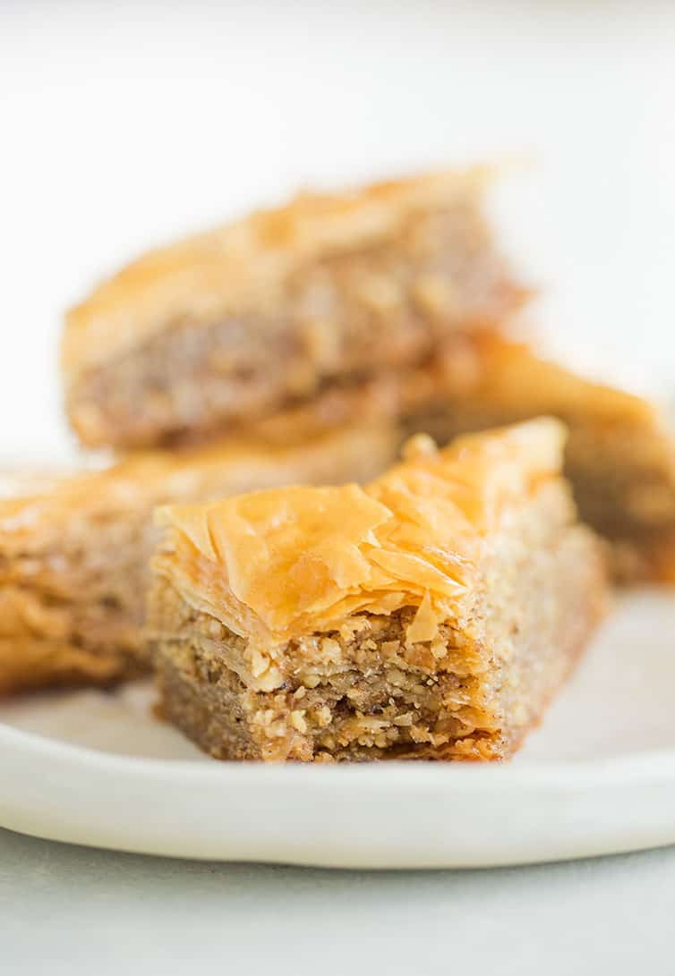 A piece of baklava on a plate with a bite taken out of it.
