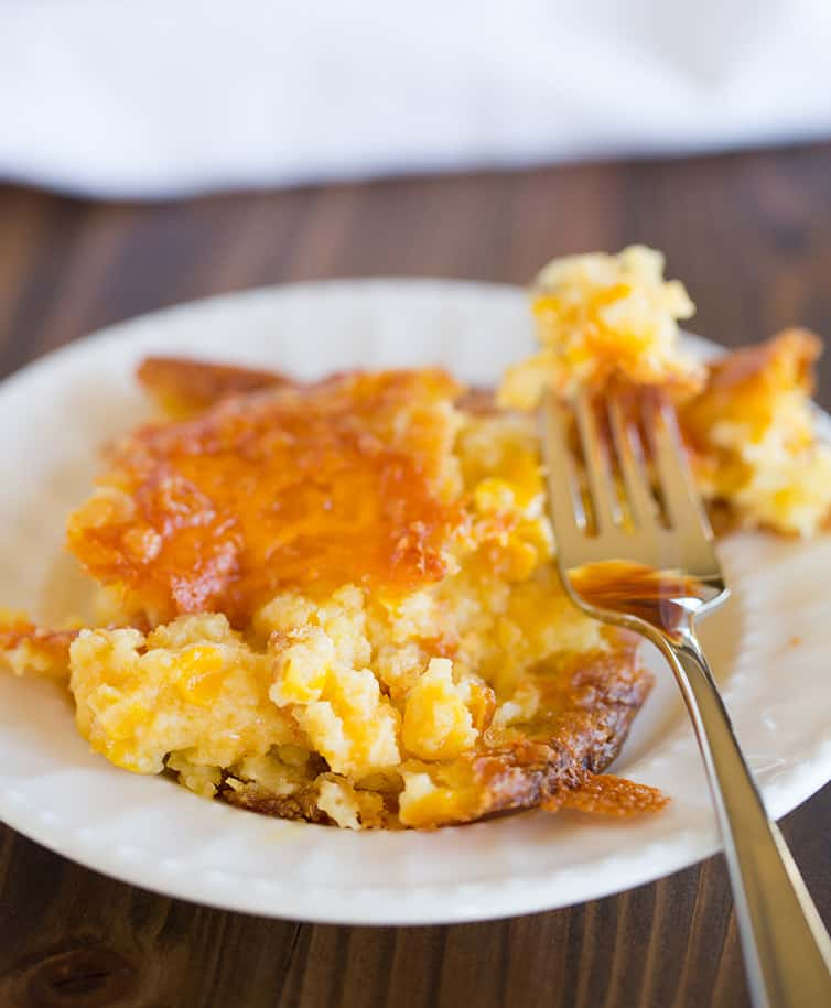 A serving of cheesy creamed corn casserole on a round plate.
