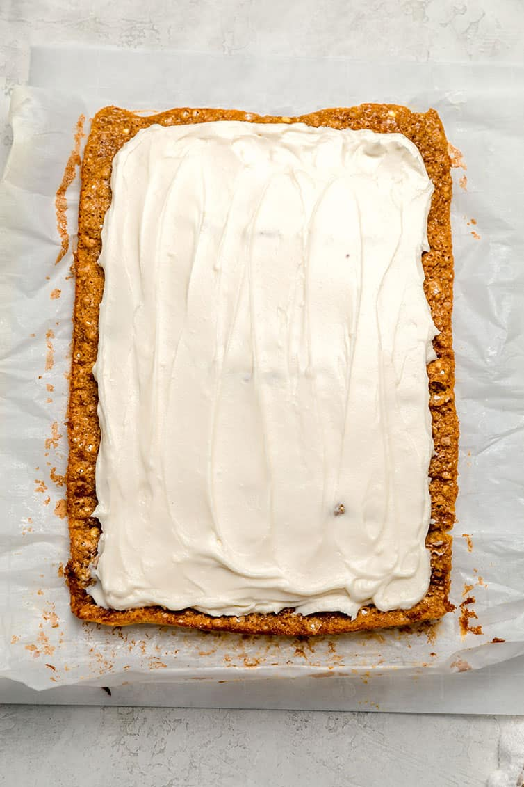 A pumpkin roll slathered with cream cheese frosting before being rolled back up.