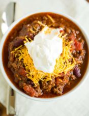A big bowl of classic beef chili topped with shredded cheddar and sour cream.