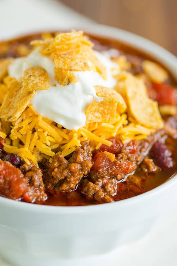 A bowl of beef chili topped with cheddar, sour cream and Fritos.