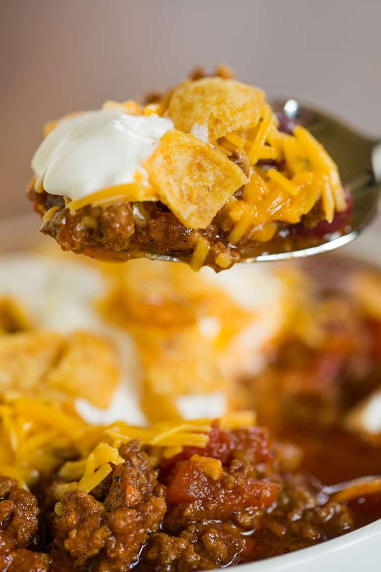 Taking a big spoonful of beef chili with cheddar, sour cream, and Fritos.