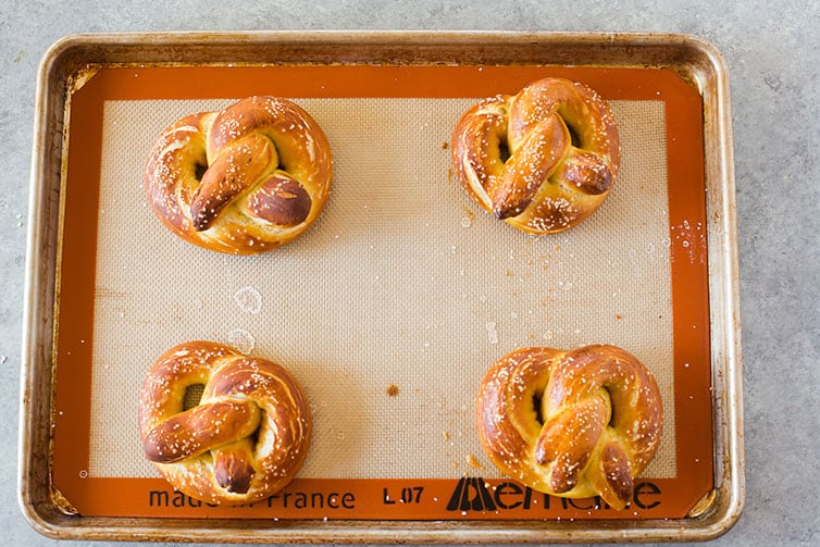 Four soft pretzels out of the oven on a baking sheet.
