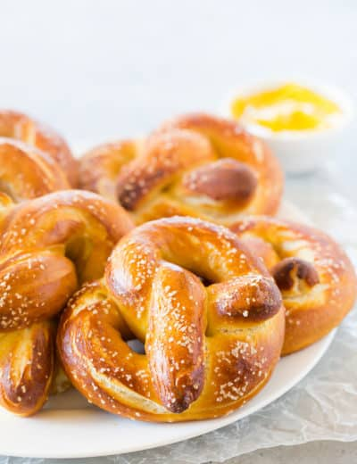 Soft pretzels on a plate with dipping mustard in the background.