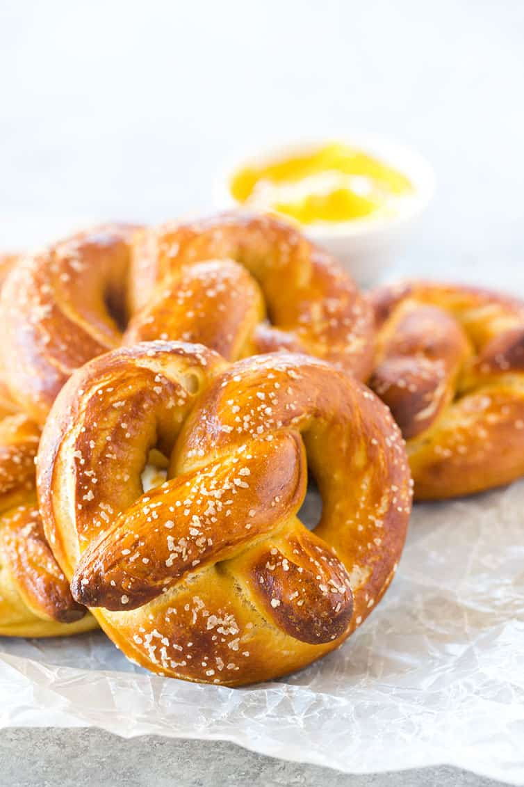 Soft pretzels on wax paper with dipping mustard in the background.