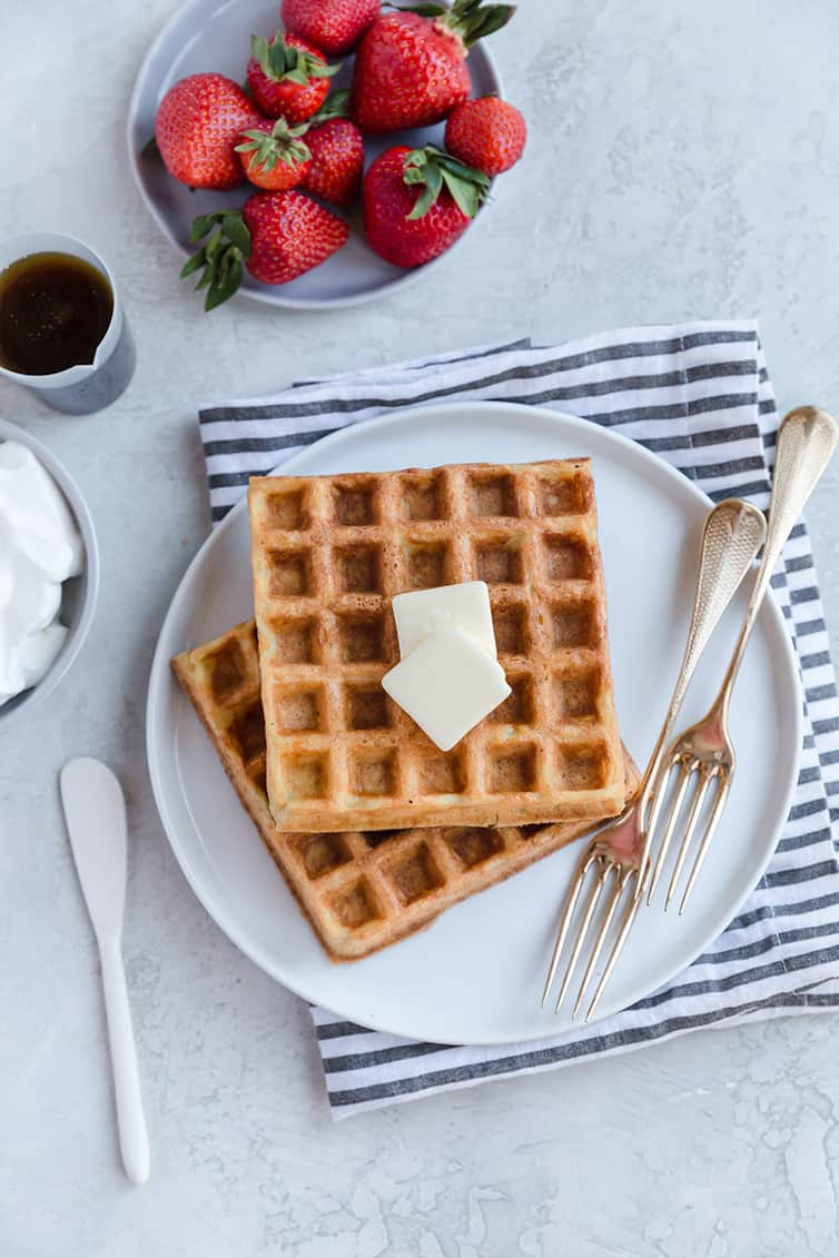 Two waffles on a plate with pats of butter on top.