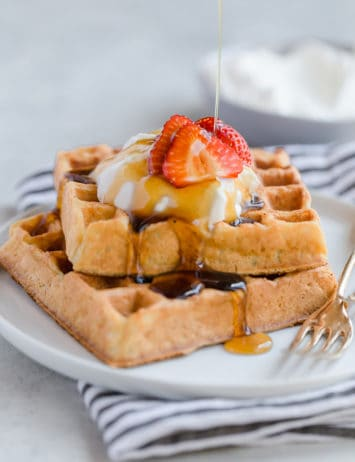 Two square waffles stacked with whipped cream and strawberries on top.