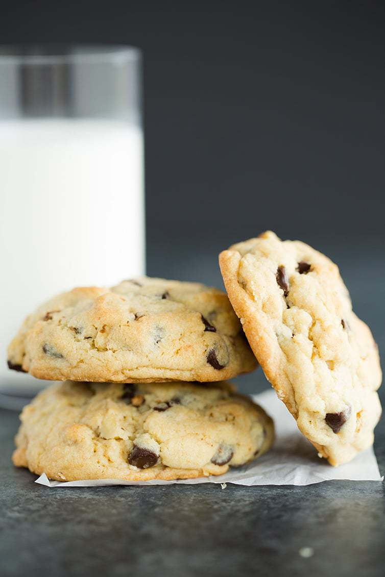 A stack of Levain chocolate chip cookies with a glass of milk.