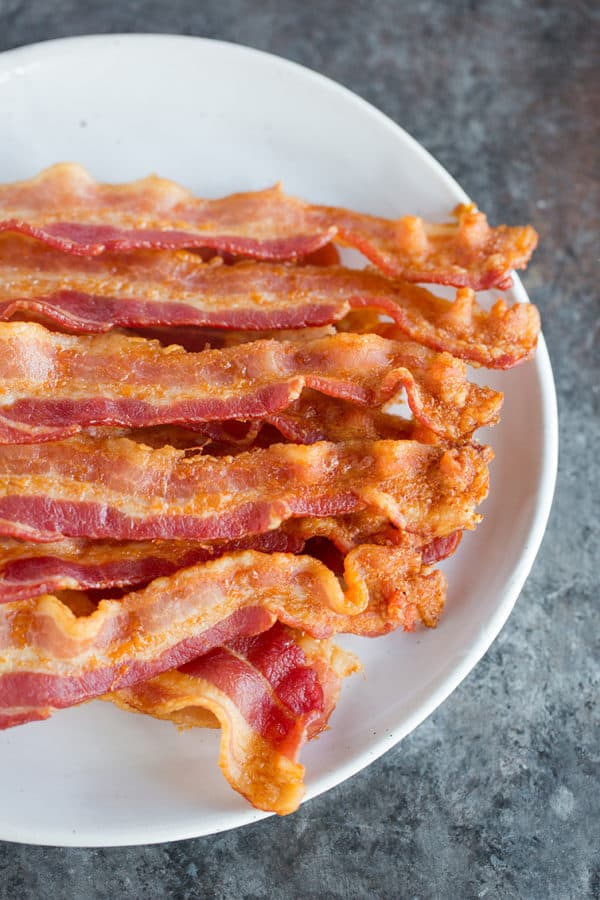 A plate with slices of oven baked bacon.