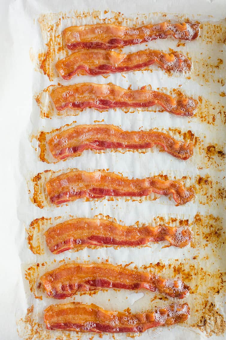 Freshly cooked oven baked bacon on a parchment-lined baking sheet.
