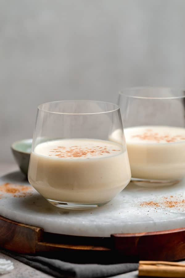 Two glasses half-filled with eggnog and a sprinkle of nutmeg.