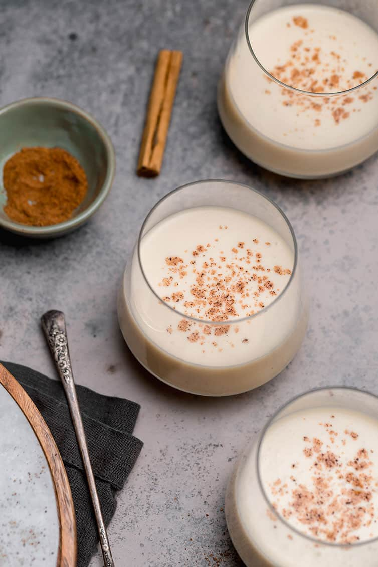 Three glasses of eggnog with a cinnamon stick and a bowl of grated nutmeg.