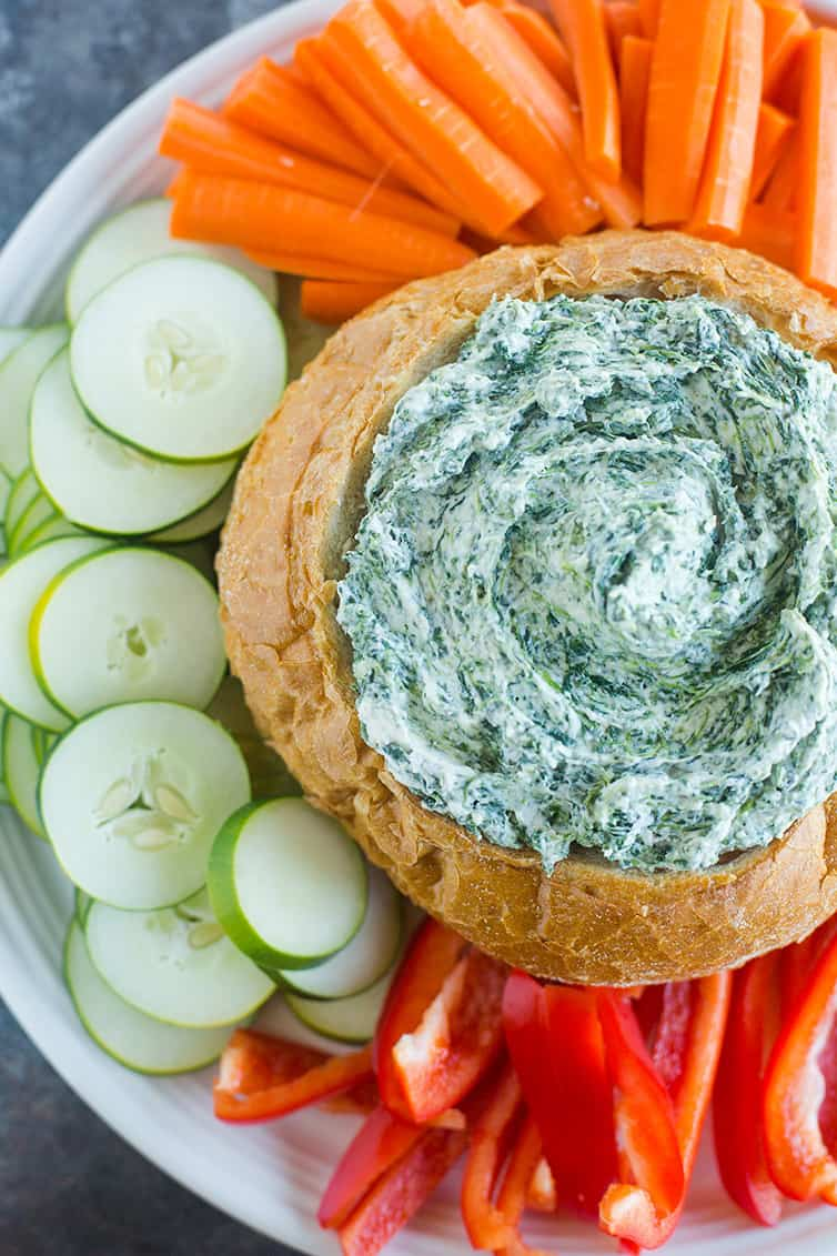 An overhead shot of spinach dip in a bread bowl with cucumbers, carrots and red peppers.