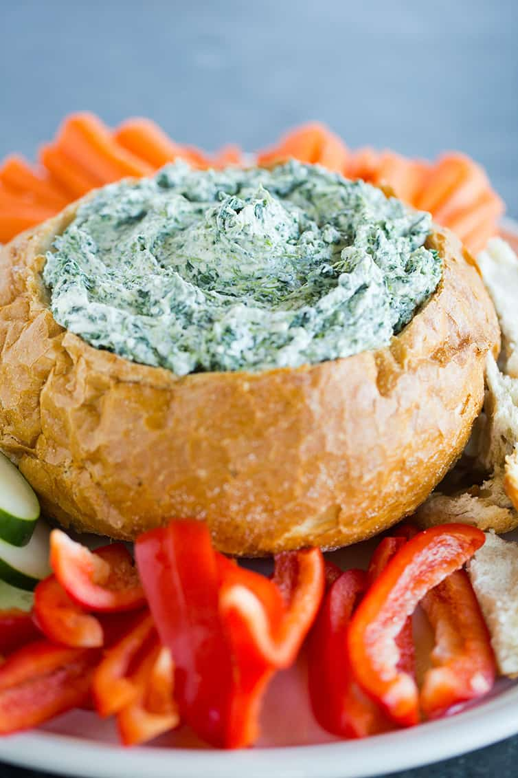 A bread bowl filled with spinach dip alongside red peppers and carrots.