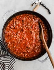 A large pot of meat sauce with a wooden spoon in it.
