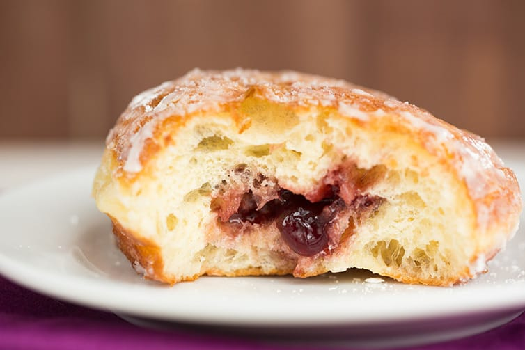 The inside of a half-eaten paczki with fruit filling.