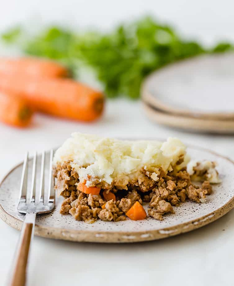 A plate of shepherd's pie with carrots and parsley in the background.