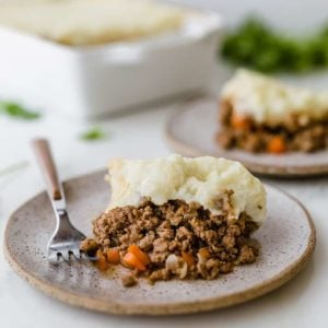Two plates with shepherd's pie and the casserole dish in the background.