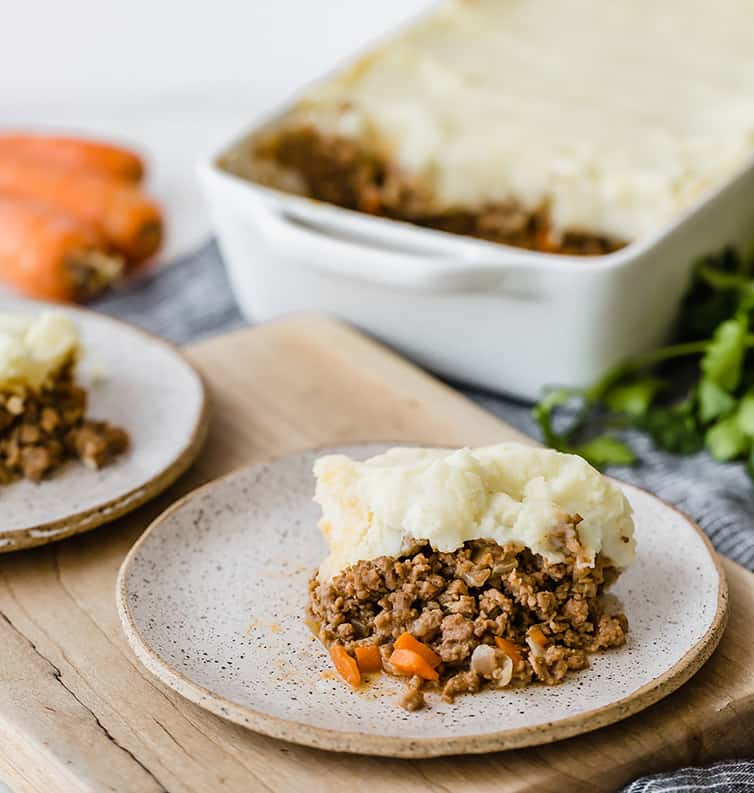 A plate of shepherd's pie with the casserole dish in the background.
