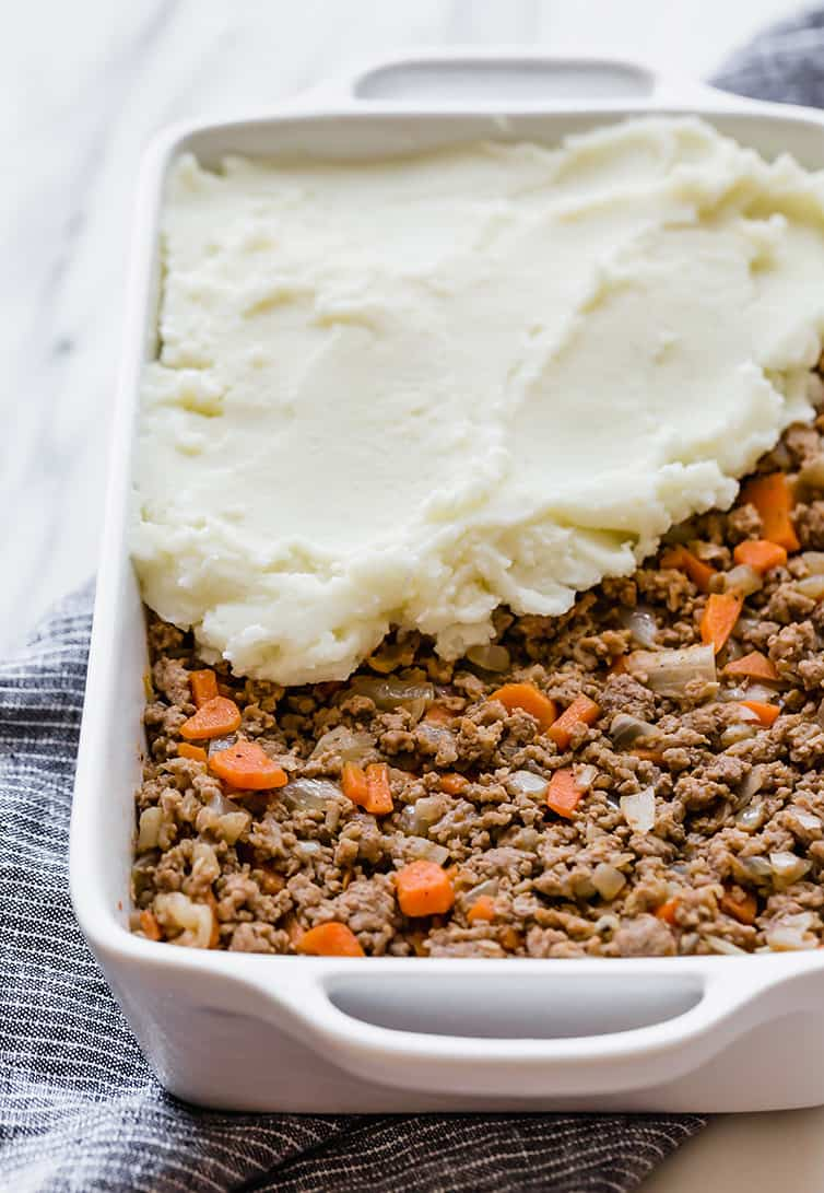 The meat mixture for shepherd's pie is in a casserole dish with the mashed potato topping being spread on top.